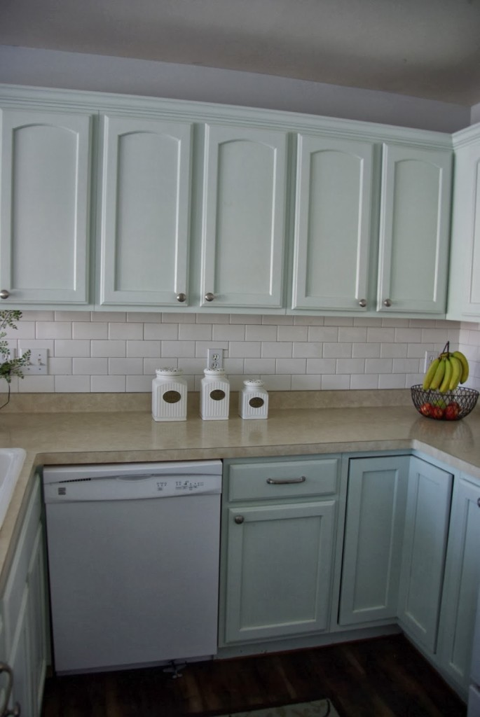 green kitchen cabinets with white subway tile