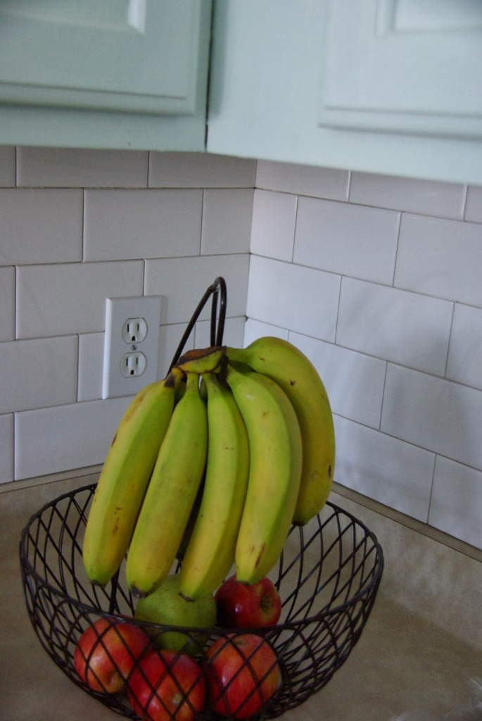 white subway tile back splash with bananas