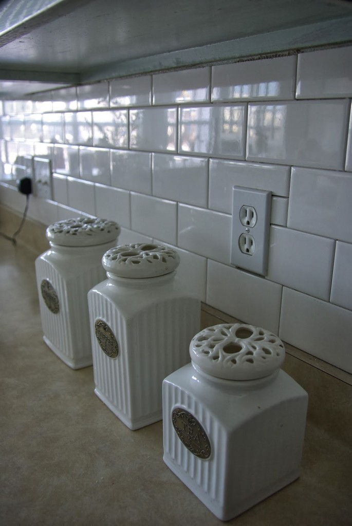 white subway tile back splash with canisters