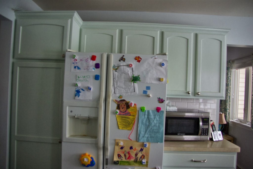green kitchen cabinets with kids art work