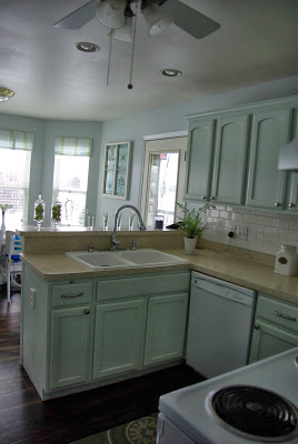green kitchen cabinets with wood floors