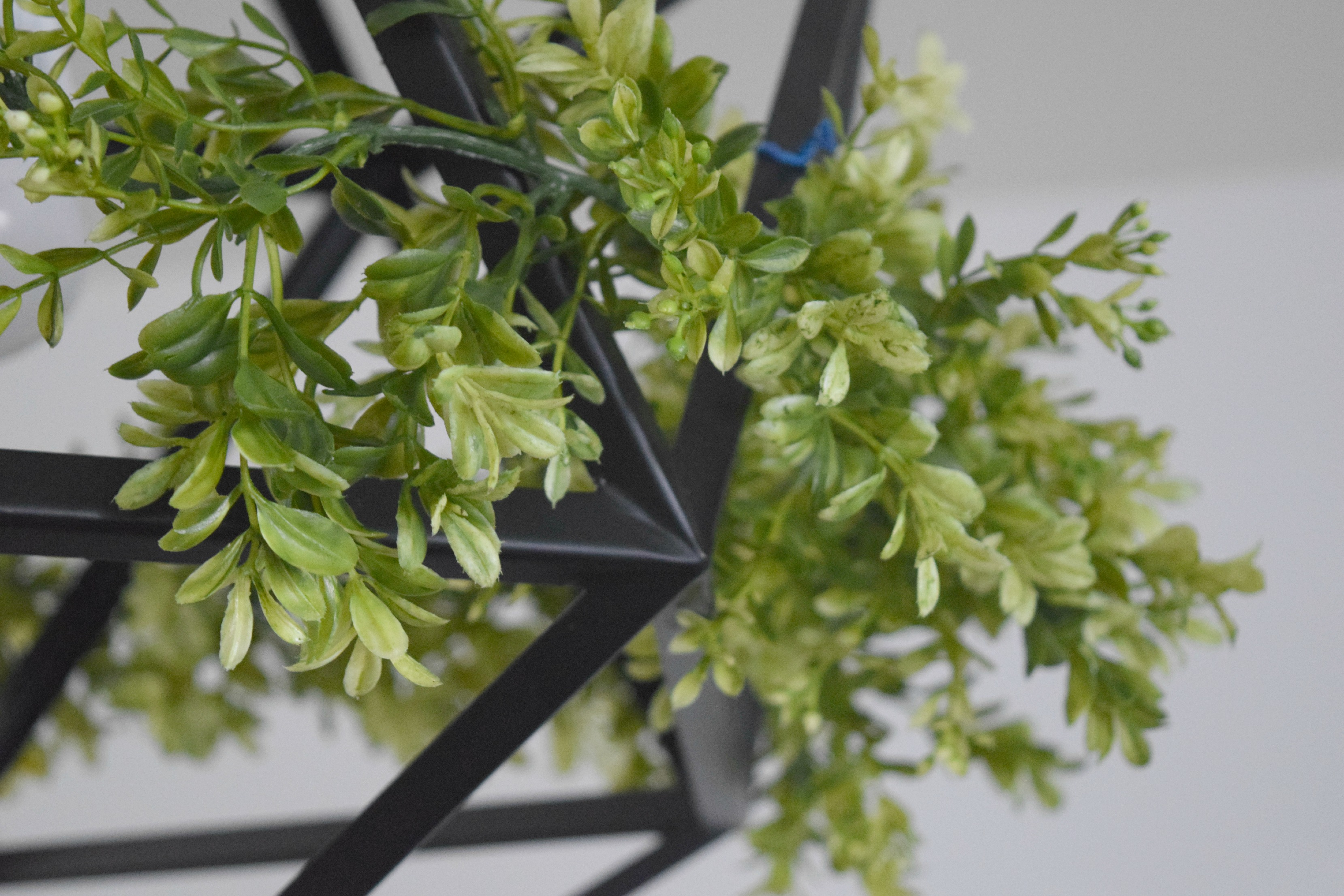 adding green christmas garland to ceiling light