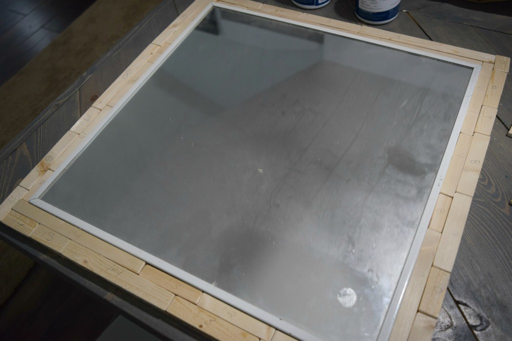 placing wood on mirror frame