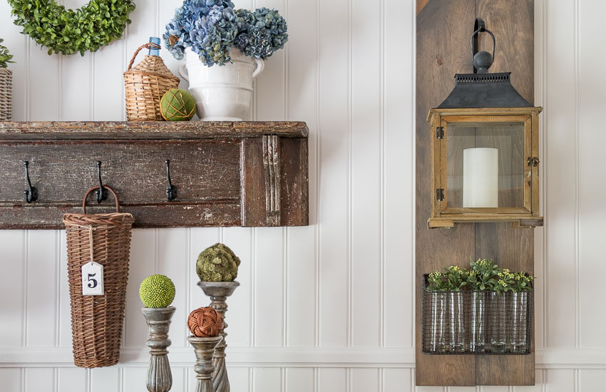 Fixer-Upper-style-diy-hanging-lantern-on-a-wood-plaque-with-a-wire-basked-and-greenery-filled-vases