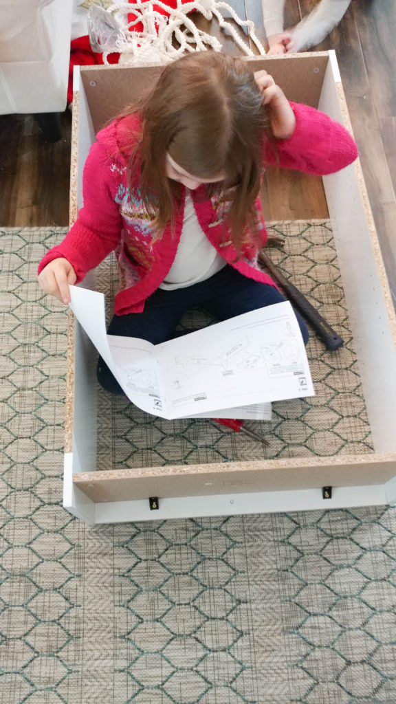 nora putting ikea cabinet together